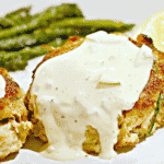 close up of crab cakes with tartar sauce on top