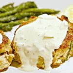 close up of crab cakes with tartar sauce on top