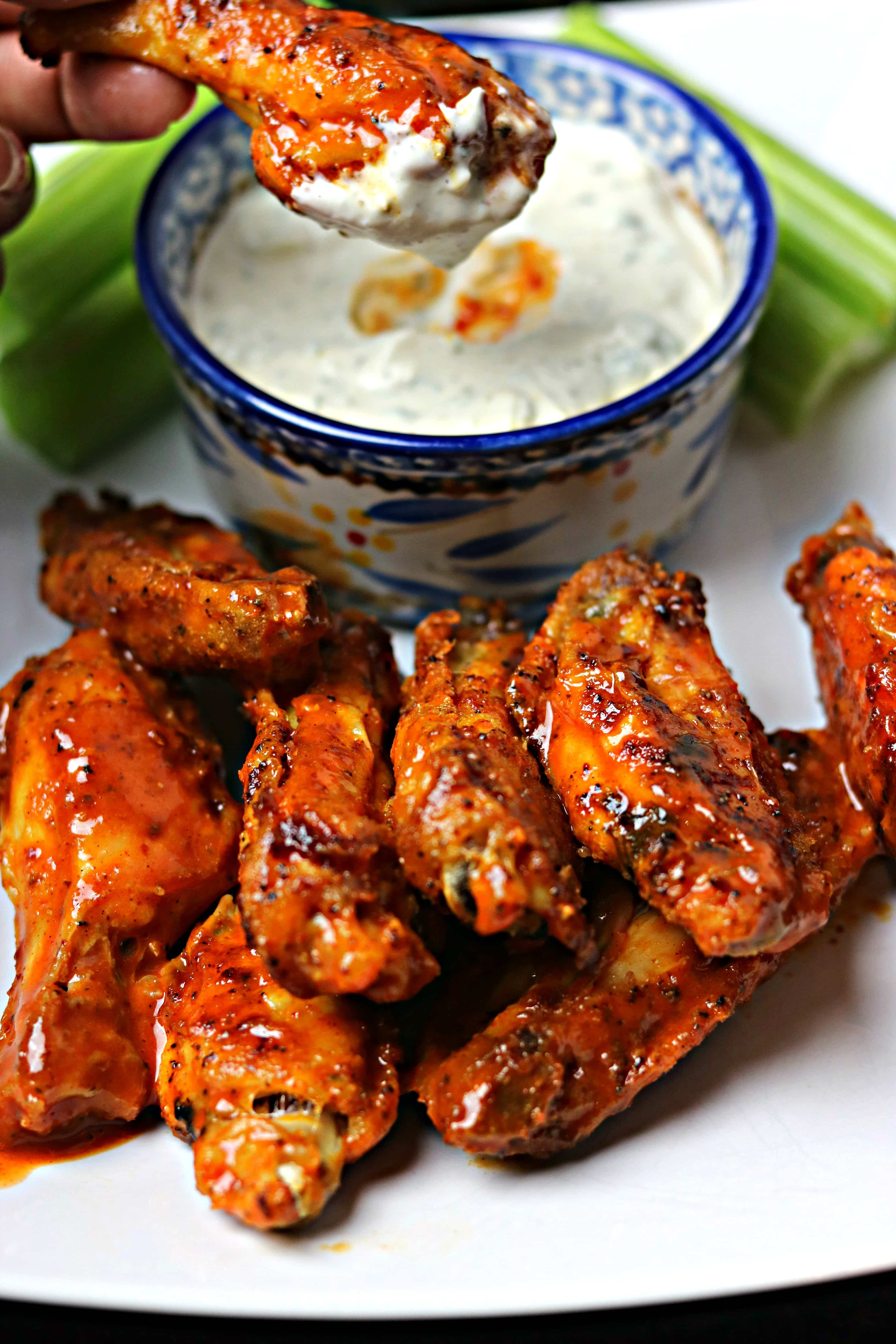 Air Fryer Buffalo Wings on a plate with celery sticks and a bowl of blue cheese dressing