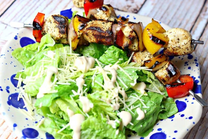 Easy grilled chicken kabobs on a plate with a Caesar salad