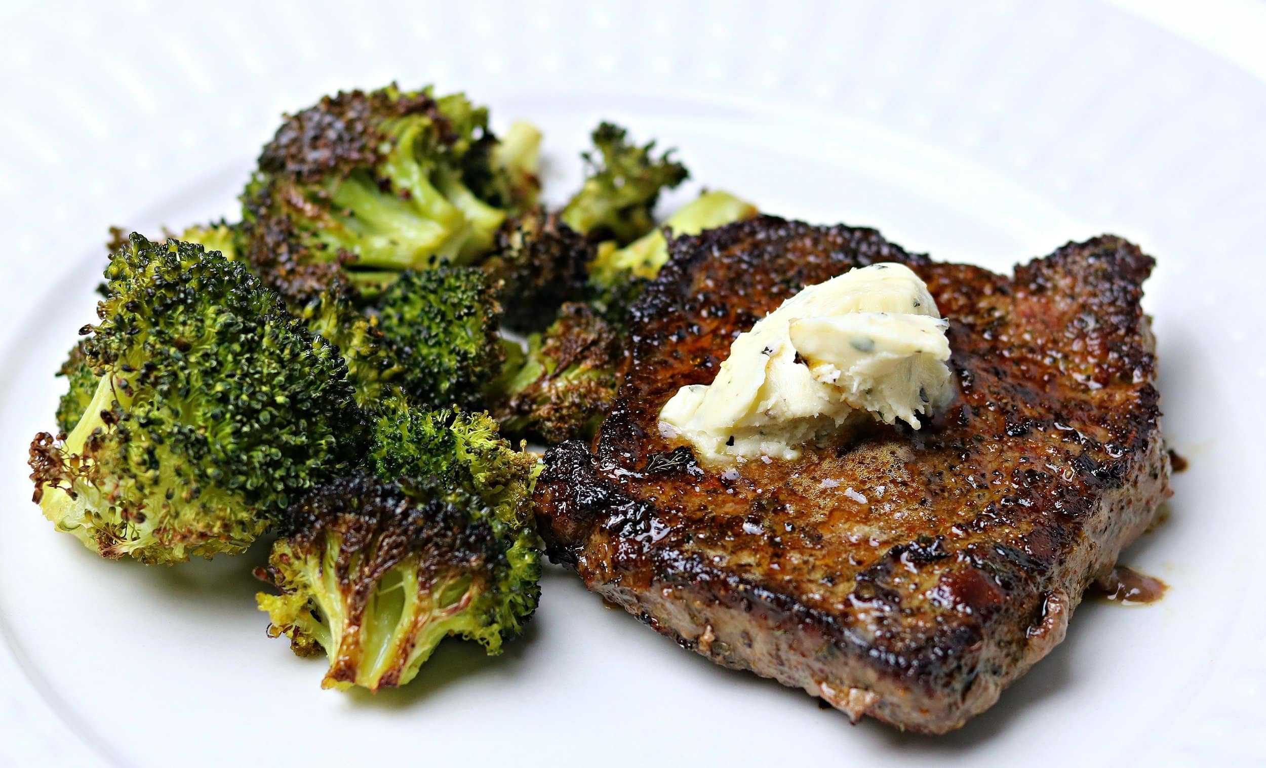 The final product of this beef top sirloin recipe - beef sirloin steak on a plate with roasted broccoli and compound butter.