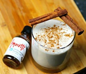 Keto Christmas Coquito in a cup with cinnamon sticks