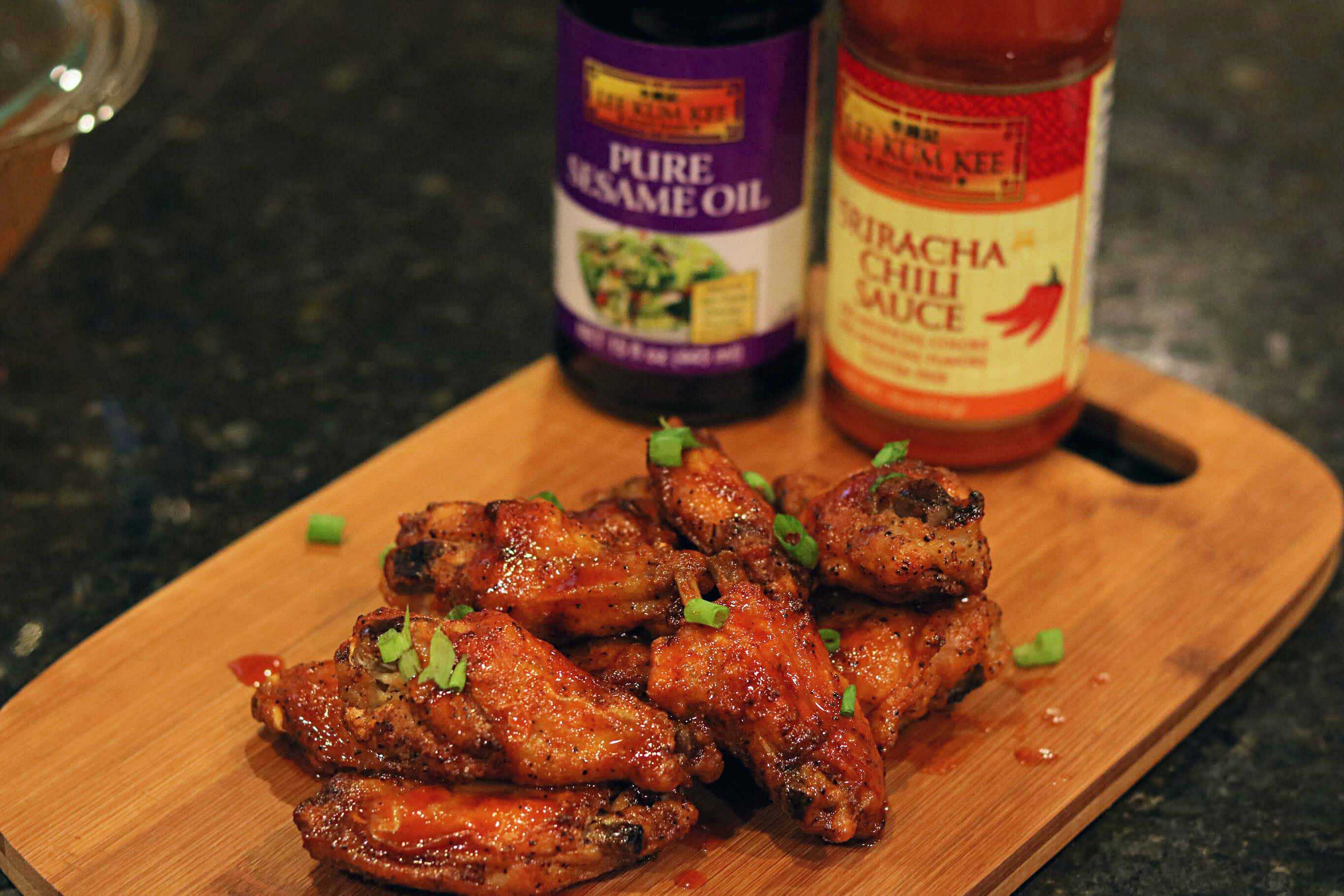 Crispy Honey Sriracha Chicken Wings on a board with Lee Rum Kee sauces