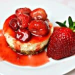 Gluten-free keto cheesecake on a white plate with strawberry sauce on top