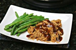 Pressure Cooker Keto BBQ Pulled Pork on a plate with green beans
