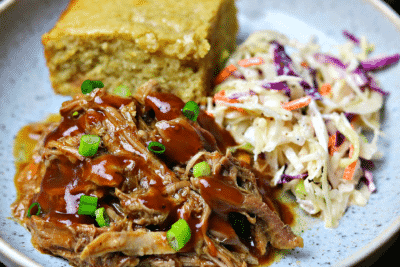 Keto BBQ Pulled Pork recipe on a plate with corn-free bread and keto coleslaw