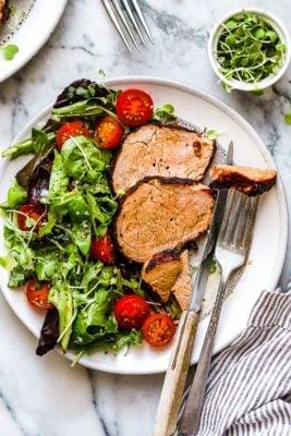 Grilled Cumin Spiced Pork Tenderloin on a plate with a salad