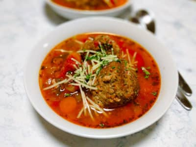 Meatball Veggie soup in white bowl with spoon and grated cheese garnish.