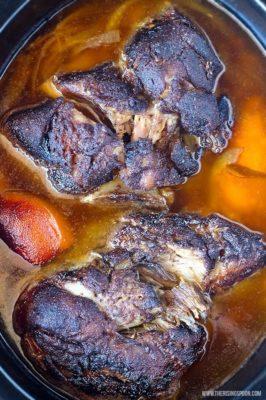 Slow Cooker Pork Shoulder in cooking pot with broth.
