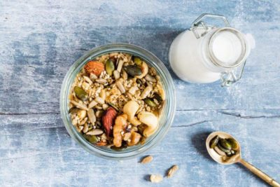 Low Carb Granola in serving bowl with milk and a spoon.