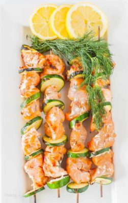 Grilled salmon kabobs on a plate with lemon slices