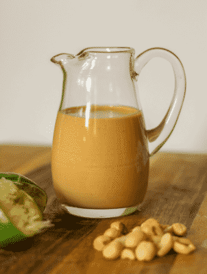 A pitcher of Creamy Thai Peanut Dressing with peanuts in foreground