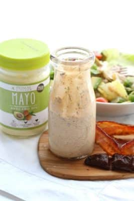 A jar of Paleo Chipotle Bacon Ranch Dressing next to Primal Kitchen Mayo and a bowl of salad