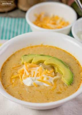 Low Carb Green Chile Enchilada Soup in white bowl with sliced avocado