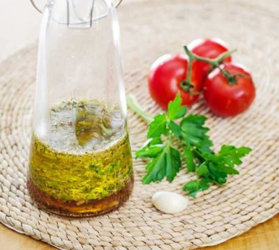 Italian Dressing in a carafe with tomatoes