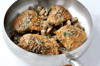 A frying pan filled with Herbed Chicken and mushrooms