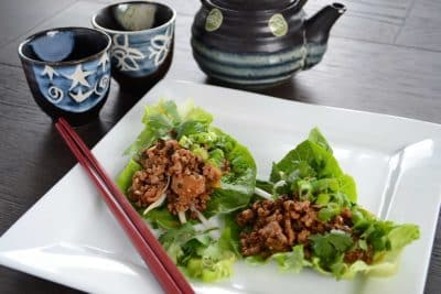 San ChoyBau in lettuce leaves on white plate with chopsticks and sake set in background
