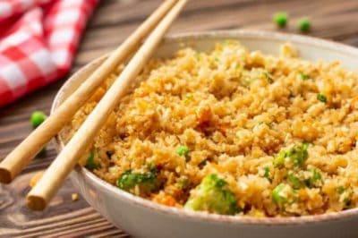 Cauliflower fried rice in white bowl with chopsticks