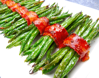 BACON WRAPPED GREEN BEANS on a white serving dish
