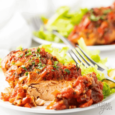 Healthy Slow Cooker Chicken Cacciatore Recipe a white plate with a fork, ready to eat.