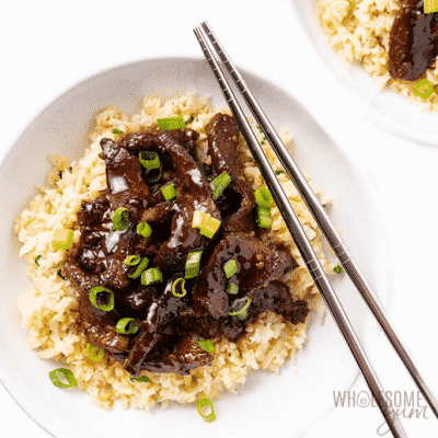 Keto Slow Cooker Mongolian Beef in white bowl with chopsticks. serving dish with metallic chopsticks