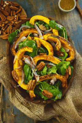 ROASTED PUMPKIN SALAD inside of a wooden bowl