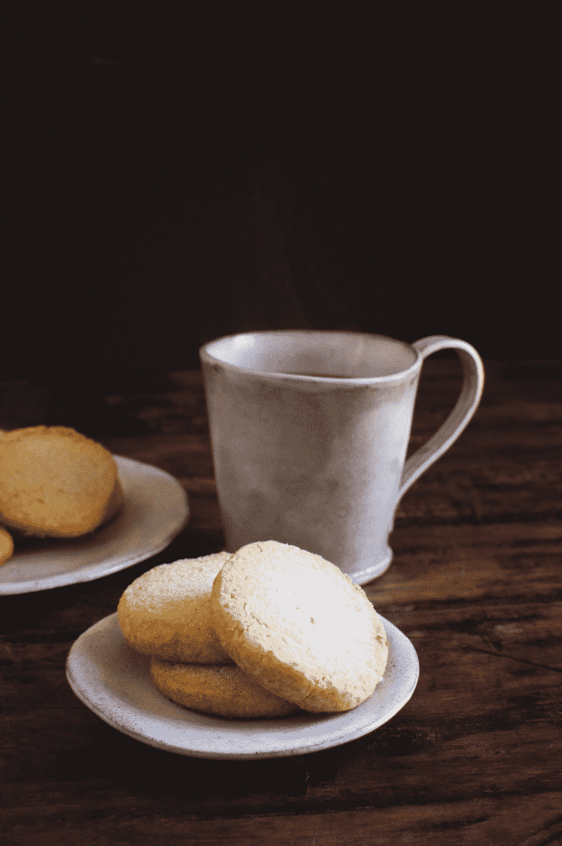 SUGAR COOKIES on small plates next to a tea cup