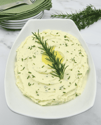 ROASTED GARLIC AND ROSEMARY MASHED CAULIFLOWER in a white serving dish