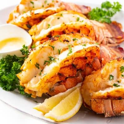 Four split lobster tails on a plate with butter and sliced lemon