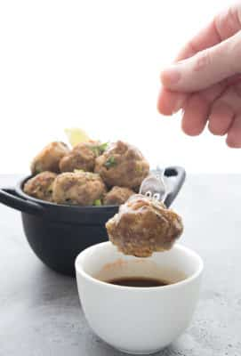 A thai meatball on a fork over a bowl of dipping sauce
