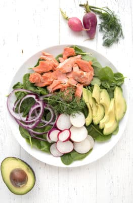 A plate filled with salmon, avocado, purple onions, radishes, and fresh spinach leaves