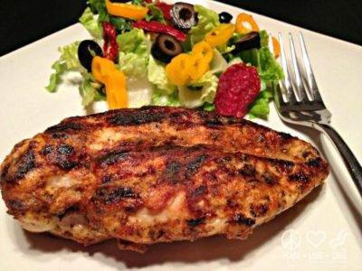 A blackened dijon chicken breast on a plate with a side of salad