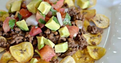 Plantain slices with ground beef, chunks of avocados and tomatoes