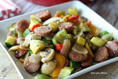 A square plate filled with sausage, peppers, mushrooms, and onions