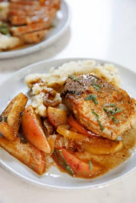 A plate with a seasoned pork chop, mashed cauliflower, and sliced apples and onions - Whole30 dinner recipe