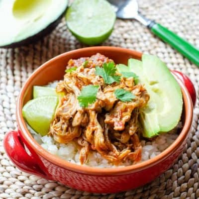 Shredded chicken in a bowl over cauliflower rice, garnished with avocado and lime slices - an easy Whole30 dinner