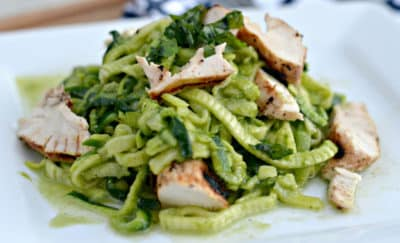 An easy Whole30 dinner idea featuring spiralized zucchini noodles with pesto sauce and chunks of chicken