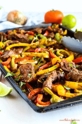 STEAK FAJITAS with sliced peppers in a black sheet pan