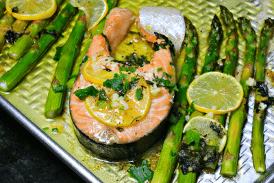 Finished salmon steak with asparagus in a pan