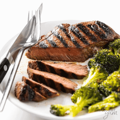 Top Sirloin Steak on a white serving dish with silverware