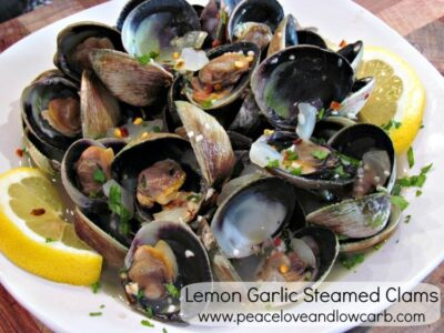 Lemon Garlic steamed clams on white plate garnished with lemon slices.