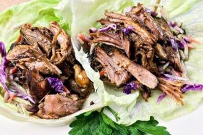 Slow Cooker Pulled Pork on two large lettuce leaves.