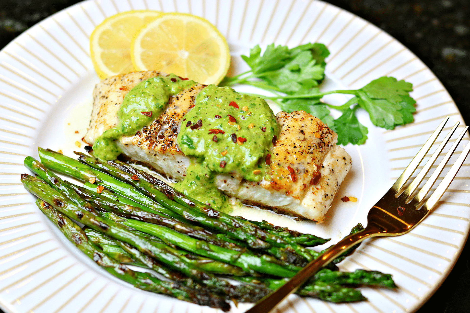 Halibut on a plate with asparagus and chimichurri sauce