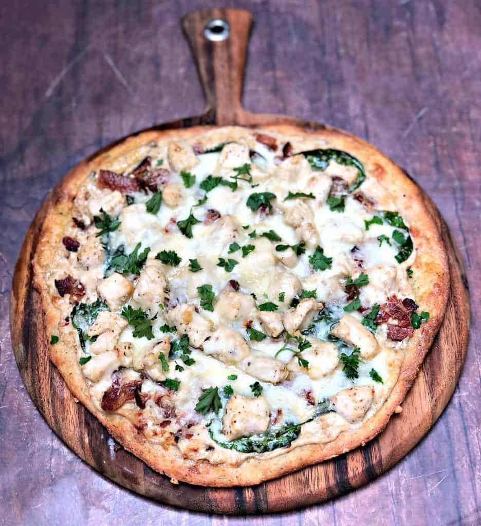 Keto Low-Carb Bacon, Chicken, Spinach Alfredo Fathead Pizza on a pizza board