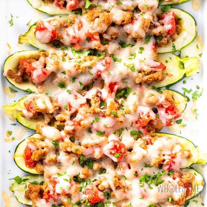 Keto Italian Sausage Stuffed Zucchini Boats on a white serving dish