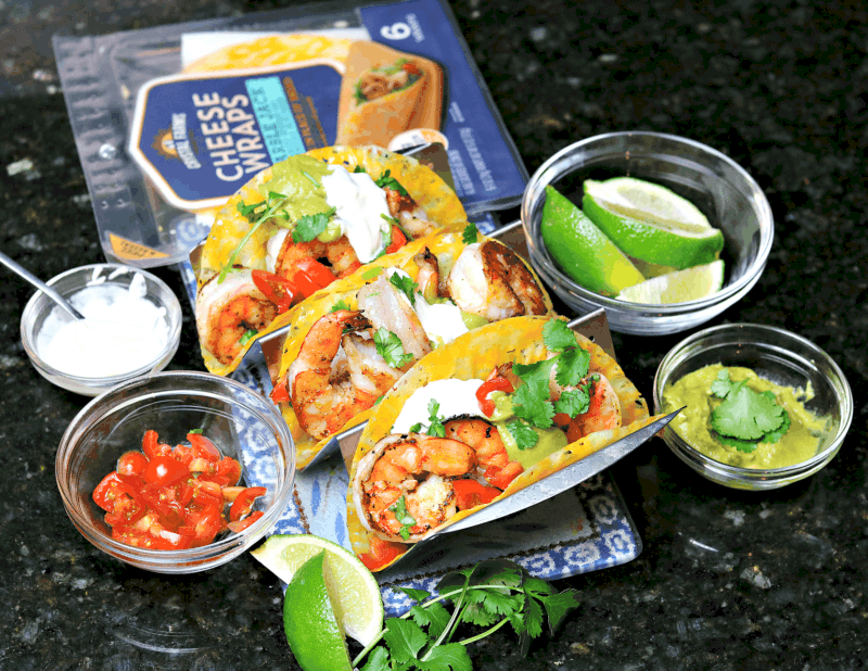 three shrimp tacos with toppings and a pack of Crystal Farms Cheese Wraps