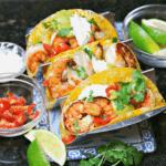 three shrimp tacos on a taco stand