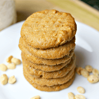 keto peanut butter cookies stacked on a white plate