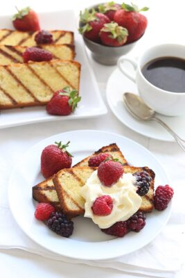 Grilled Pound Cake with Mixed Berries on a white plate and a cup of coffee