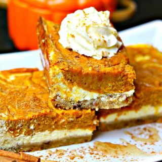 close-up of three keto pumpkin pie cheesecake bars stacked on top of each other
